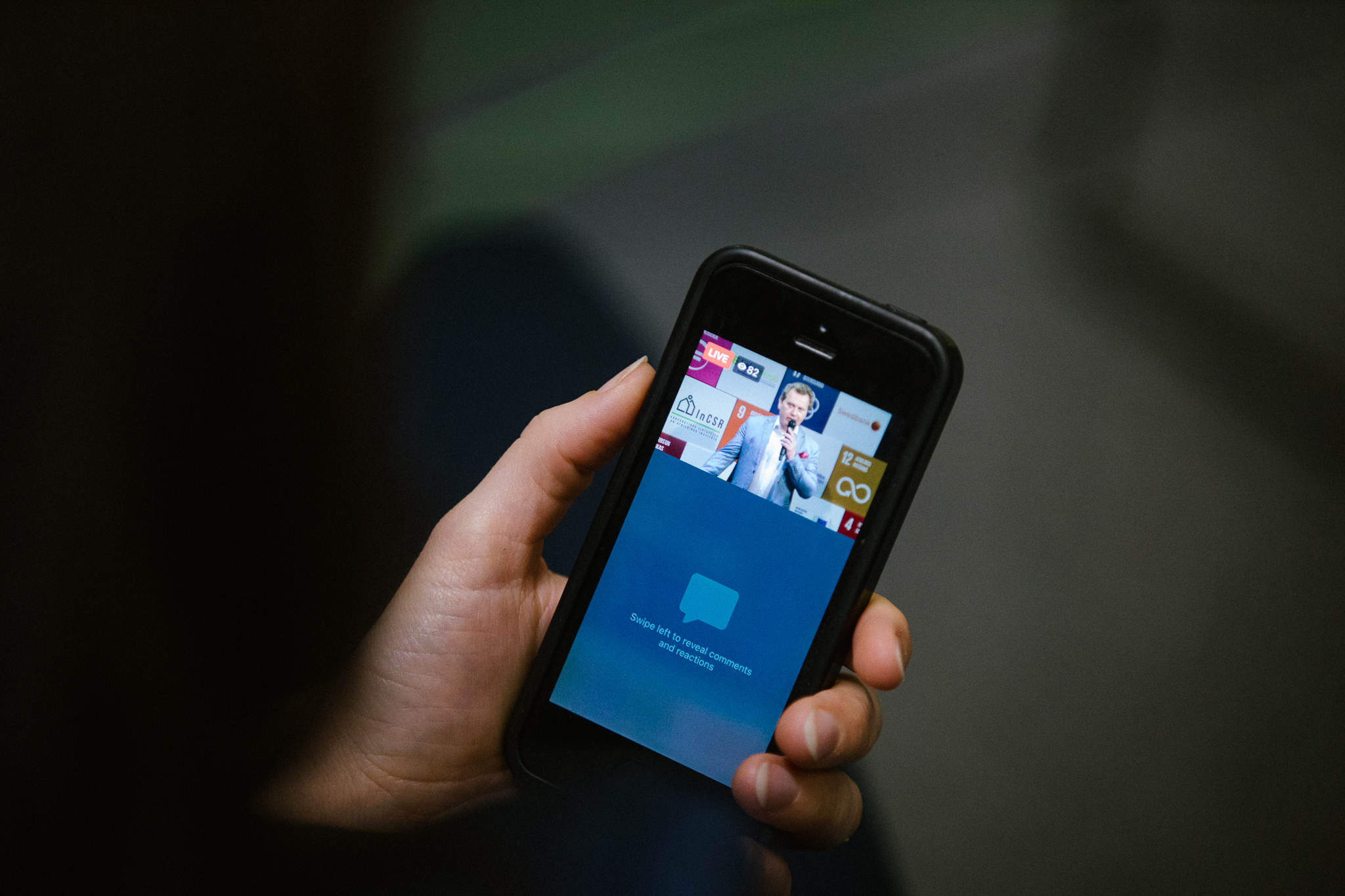 Roka, kurā ir mobilais tālrunis, kura ekrānā ir redzama Atbildīgu ideju tirgus 2020 tiešraide