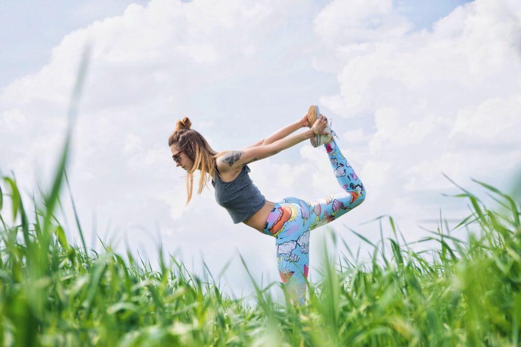 Jauna sieviete krāsainās sporta biksēs stiepj kāju uz aizmuguri, stāvot pļavā. Fonā gubu mākoņi.