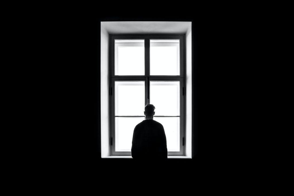 Cilvēks tumšā telpā vientuļi stāv pie loga