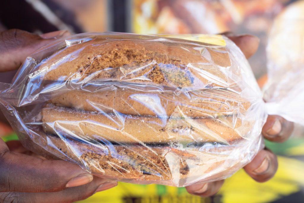 Cilvēka rokas tur četras maizītes, kas iesaiņotas maisiņā.