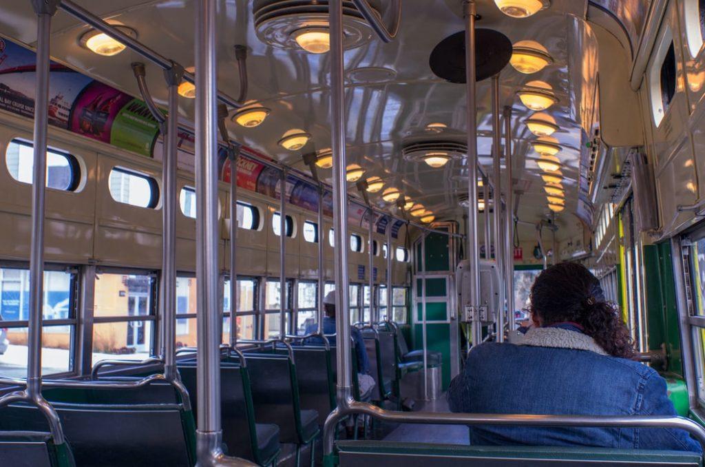 Autobusa salons, kurā ar ievērojamu atstarpi sēž divi pasažieri - sieviete un vīrietis.
