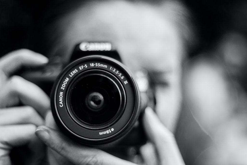 Melnbalta fotogrāfija. Tuvplānā redzams fotoaparāta objektīvs, ko tur cilvēks. Viņa seja ir izplūdusi.