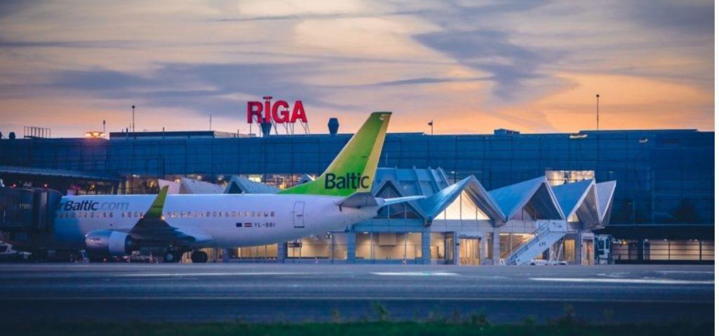 """Starptautiskās lidostas """"Rīga"""" terminālis. Priekšplānā redzama """"AirBaltic"""" lidmašīnas aste."""