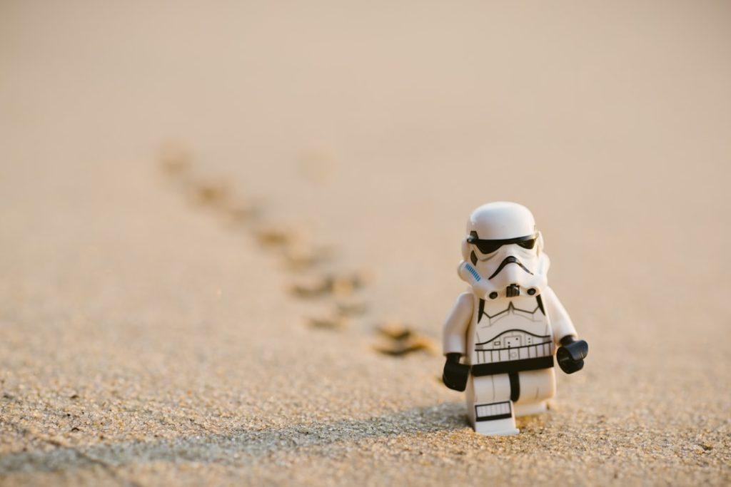 """Pasaulē slavenās """"Zvaigžņu karu"""" sākas tēls, ko dēvē par šturmotāju, iet pa smiltīm, atstājot aiz sevis pēdu nospiedumus. Viņam visapkārt redzamas smiltis, kas simbolizē tuksnesi. Šturmotājs ir veidots kā LEGO konstruktora figūriņa."""