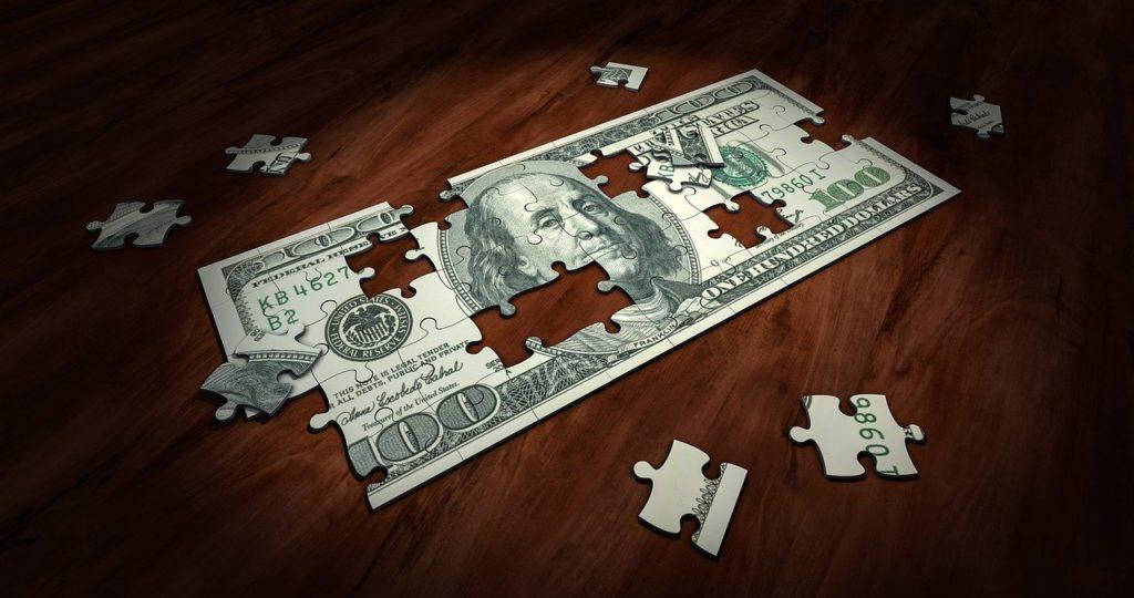 Uz galda stāv puzzle ar 100 dolāru banknotes attēlu. Tā ir gandrīz salikta, atlikuši vēl daži gabaliņi, kas jāieliek īstajās vietās.