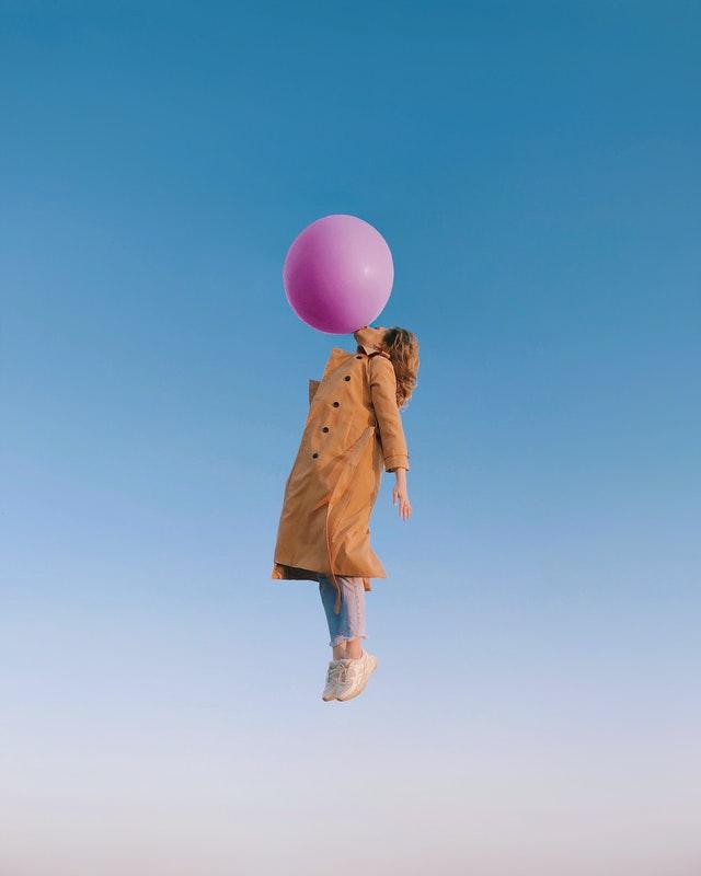 Pavasarīgi ģērbusies sieviete lido mākoņos, turoties ar muti pie liela rozā krāsas balona.