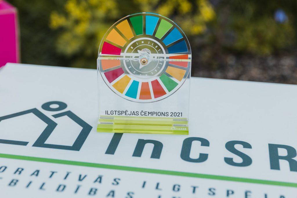 """Priekšplānā ir balva """"Ilgtspējas čempions 2021"""" - caurspīdīgs organiskā stikla taisnstūris, kurā iestiprināts rotējošs apliks, uz kura uzdrukāts ANO ilgtspējīgu attīstības mērķu simbols. Balva novietota uz baltas pamatnes, uz kuras ir uzdrukāts Korporatīvās ilgtspējas un atbildības institūta logo. Fonā ir izplūdis dabas skats."""