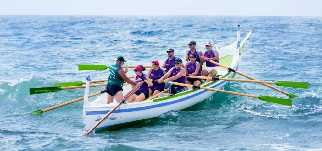 Jūrā viļņus šķeļ sacensību laiva, kurā atrodas astoņi cilvēki - septiņi airē, bet viens viens, kurš atrodas priekšplānā, uzrauga procesus, dod komandas.